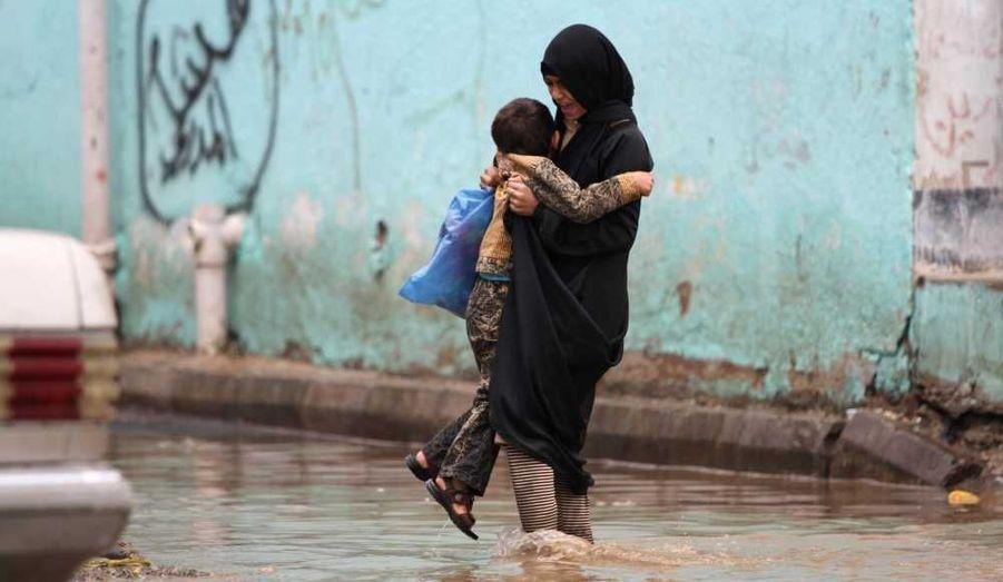 Une fille et son frère essayent de marcher dans une rue inondée de Sanaa.