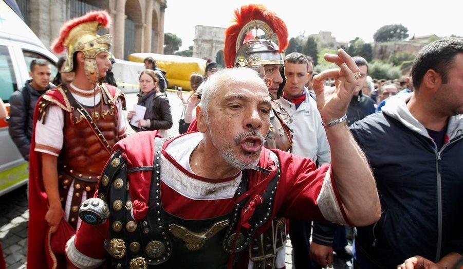 """Près de 50 personnes en costume de centurions sont allées manifester devant le Colisée de Rome. Ces """"comédiens"""", payés au noir pour poser avec les touristes réclament un statut officiel de la part de la mairie qui a voté un arrêté le 4 avril visant à leur interdire d'approcher les touristes. Ils sont en effet accusés accusés de les harceler et de les arnaquer en pratiquant des prix scandaleusement élevés. En outre, ils porteraient aussi préjudice à l'image de la glorieuse armée romaine."""
