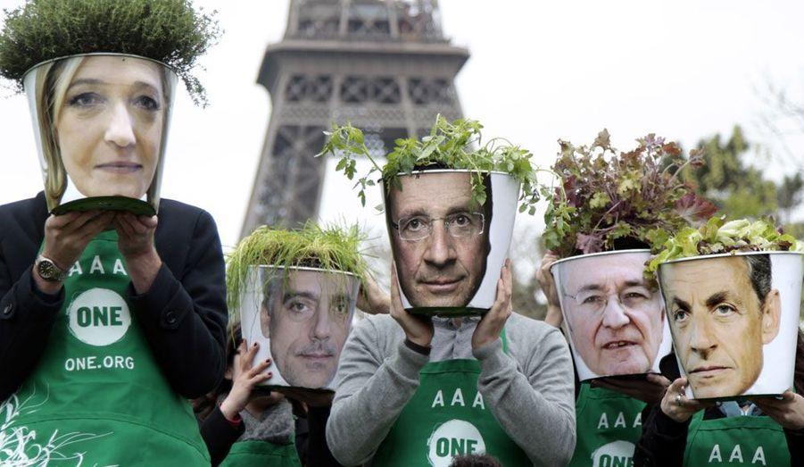 Les membres de l'association «ONE» soulèvent des pots de plantes décorés par les photos des candidats français à la présidentielle de 2012. Leur action vise à mettre en avant la faim dans le monde et la pauvreté.