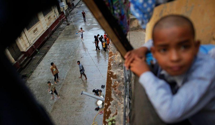 Un garçon regarde depuis le balcon d'un immeuble datant de l'époque coloniale des personnes célébrant la fête de l'eau dans le centre de Yangon, en Birmanie.