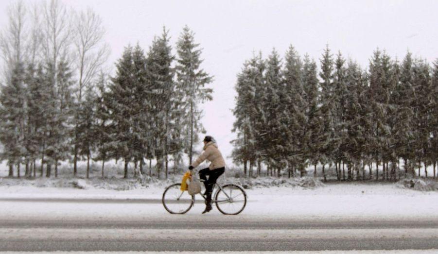 Une femme à vélo, pendant de fortes chutes de neige près du village de Novye Chemodany, à l'Est de Minsk, en Biélorussie.
