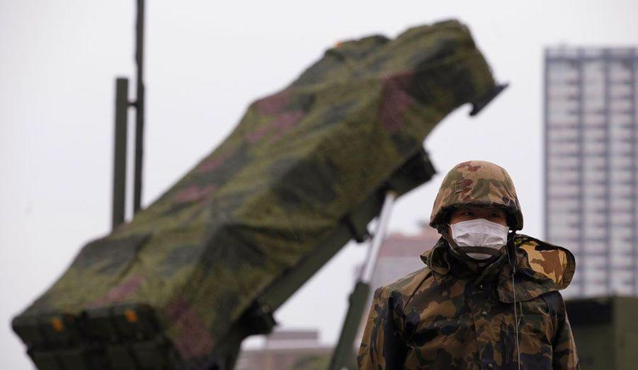 Un soldat de l'armée japonaise devant un lanceur de missiles sol-air Patriot, à Tokyo. Les autorités japonaises ont pré-positionné ces engins, capables d'abattre des missiles balistiques, alors que la Corée du Nord s'apprête à procéder au tir d'une prétendue fusée qui pourrait en fait être un prototype d'arme. Tokyo a averti Pyongyang: si l'engin survole l'espace aérien japonais, il sera détruit.