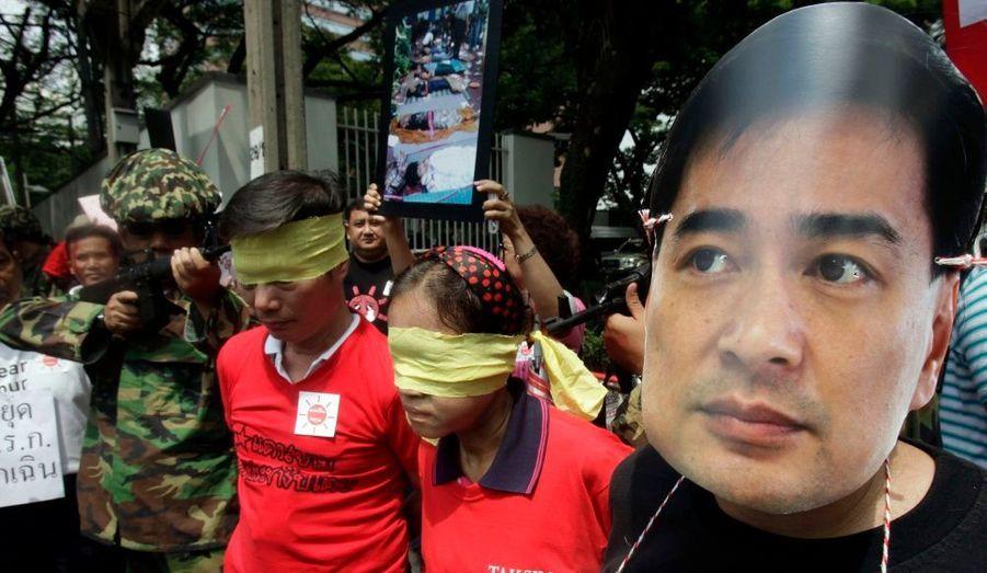 """Lors d'une manifestation des """"chemises rouges"""" antigouvernementales, un homme porte un masque du Premier ministre Abhisit Vejjajiva, tandis que d'autres se moquent de la rigueur des autorités Thaïlandaises. Mardi, le procureur général a annoncé la dissolution du parti démocrate. Une décision qui pourrait faire bannir le Premier ministre de la vie politique pour une durée de cinq ans."""