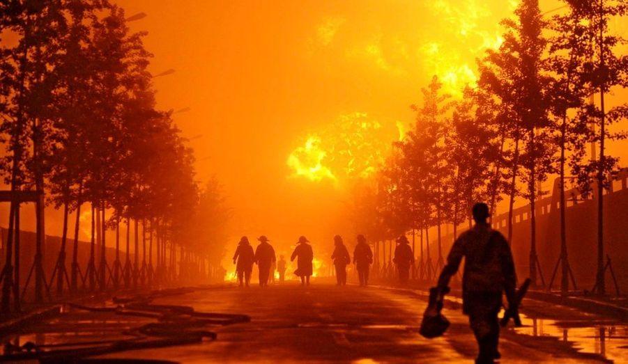 Après avoir tenté d'éteindre le feu pendant près de 15 heures, les pompiers marchent près de gigantesques flammes causées par l'explosion de deux oléoducs dans le port de Dalian, dans la province du Liaoning, au nord de la Chine, au petit matin du 17 juillet 2010.