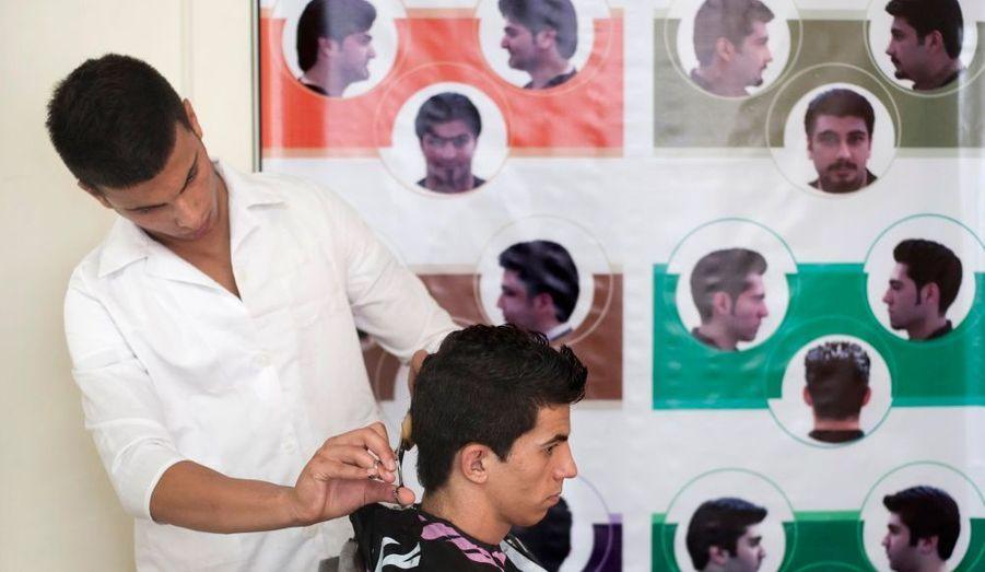 En Iran, les hommes et les femmes ne doivent pas se faire couper les cheveux n'importe comment. Le gouvernement iranien a établi une liste de coupes «acceptables». Derrière ce coiffeur et son client à Téhéran, une affiche rappelle quelles sont ces quelques coupes.
