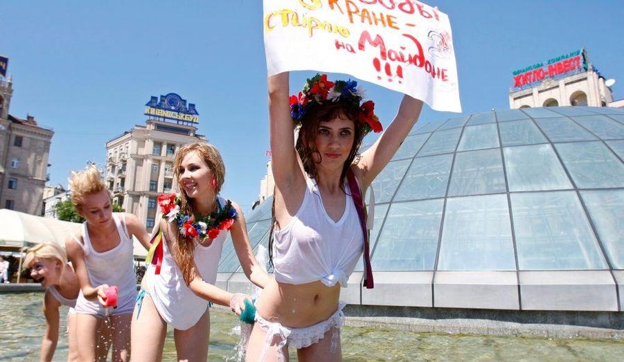 """Des militantes de l'organisation des droits des femmes """"Femen"""" protestent dans une fontaine sur la place de l'Indépendance dans le centre de Kiev (Ukraine). Ces femmes sont contre les coupures annuelles d'eau chaude de la ville. En effet, chaque année pendant plusieurs semaines, l'approvisionnement en eau chaude est coupé pour permettre aux travailleurs de réparer les tuyaux et l'équipement. """"Il n'y a pas d'eau dans le robinet, je fais ma lessive sur la place"""", peut on lire sur la pancarte."""