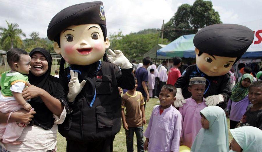 Les mascottes de l'armée thaïlandaise, dont l'objectif symbolique est de rendre les soldats familiers aux habitants de cette région trouble, jouent avec des enfants musulmans dans un village au sud de la province de Yala, le 17 juillet 2010.