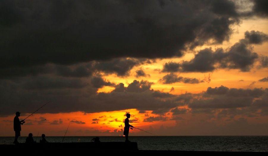 Des Cubains profitent d'un sublime coucher de soleil pour aller pêcher à La Havane.
