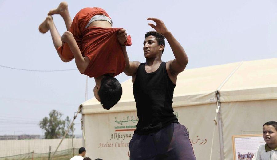 Un instructeur du Théâtre Nomade de Rabat apprend à un enfant à faire des saltos. Ce genre de théâtre est courant au Maroc, et ces ateliers sont organisés dans les quartiers les plus pauvres. On apprend aux enfants la danse, la contorsion et diverses acrobaties. Ils se reproduisent ensuite dans des hôtels ou spectacles et gagnent un peu d'argent, mais vieillissent avec de graves problèmes de dos et d'ossature.