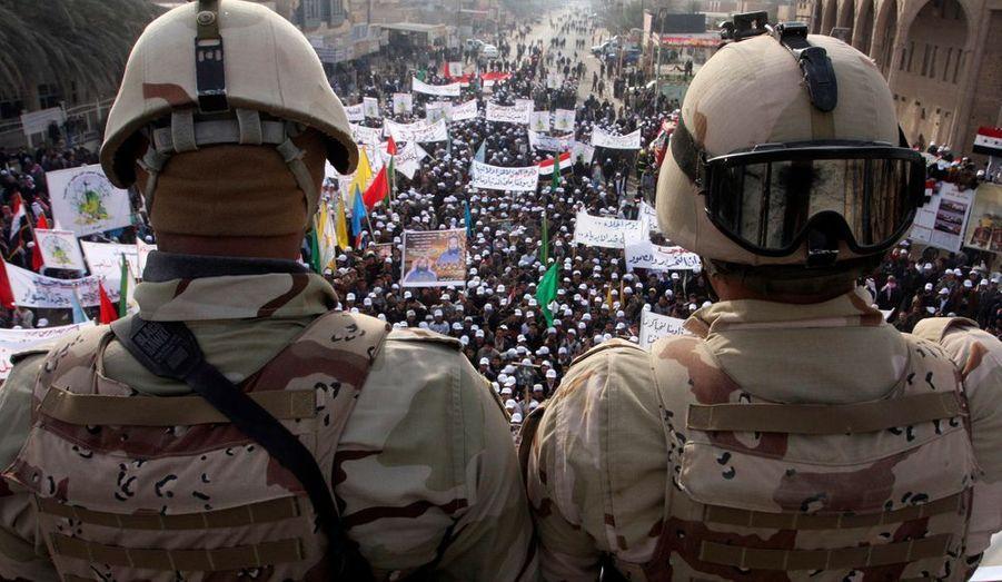 Des soldats irakiens surveillent un rassemblement célébrant le départ des troupes américaines de Falloujah, à 50 km à l'ouest de Bagdad. Des centaines de manifestants ont défilé en entonnant des slogans anti-américains, dans cette ville qui vu longtemps le bastion de la rébellion hostile aux troupes occidentales et le théâtre de violents affrontements, depuis 2003.