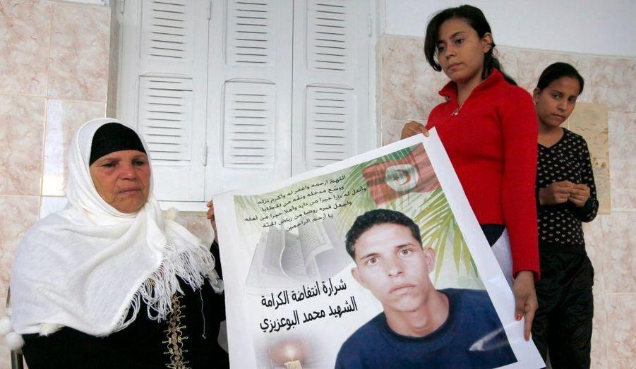 Manoubia Bouazizi et ses deux filles, Samia et Besma, devant un portrait de Mohamed en octobre dernier. Le 17 décembre 2010, ce vendeur ambulant s'est immolé par le feu devant le siège du gouvernorat de la ville de Sidi Bouzid, en Tunisie. Son geste a déclenché un immense mouvement de contestation dans le pays, à l'origine du Printemps arabe.