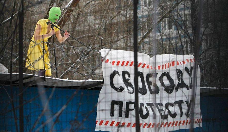 """Une membre du groupe féministe radical """"Pussy Riot"""" proteste contre la détention d'activistes sur le toit d'un immeuble, à proximité du lieu où ces derniers sont retenus aux côtés de grandes figures de l'opposition comme Ilya Yashin et Alexei Navalny. Ils ont été tous les deux condamnés à 15 jours de prison pour leur rôle dans les manifestations dénonçant les fraudes aux dernières élections législatives. On peut lire sur sa bannière : """"La liberté de protester"""".Les manifestations de l'opposition se multiplient depuis la victoire du parti de Vladimir Poutine aux dernières législatives."""