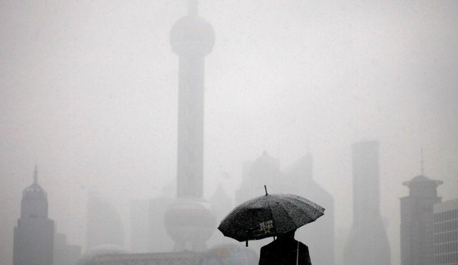 Un homme admire le quartier d'affaires de Shanghai, pris dans une tempête de neige. Selon les prévisions météorologiques rapportées par les médias, la ville sera frappée par une chute des températures à partir de jeudi.