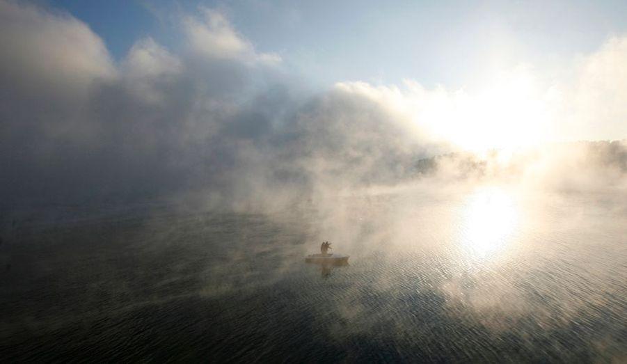 Deux habitants traversent la baie de Shumikha, en Sibérie, sur leur petite embarcation. Il fait- 23°c.