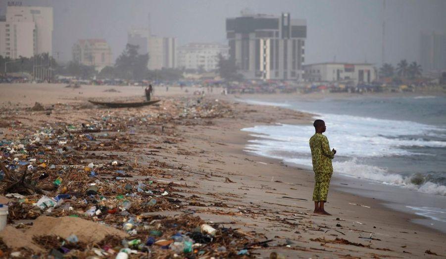 Un homme se tient sur une plage de Lagos, recouverte de détritus, au Nigeria.