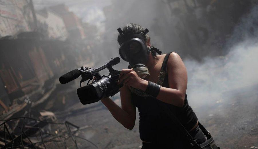 Un cameraman brave la fumée pour capter des images de l'incendie qui ravage le marché de Comayaguela, à Tegucigalpa. Une deuxième catastrophe au Honduras, après le feu qui a décimé la population carcérale d'une prison la semaine dernière.