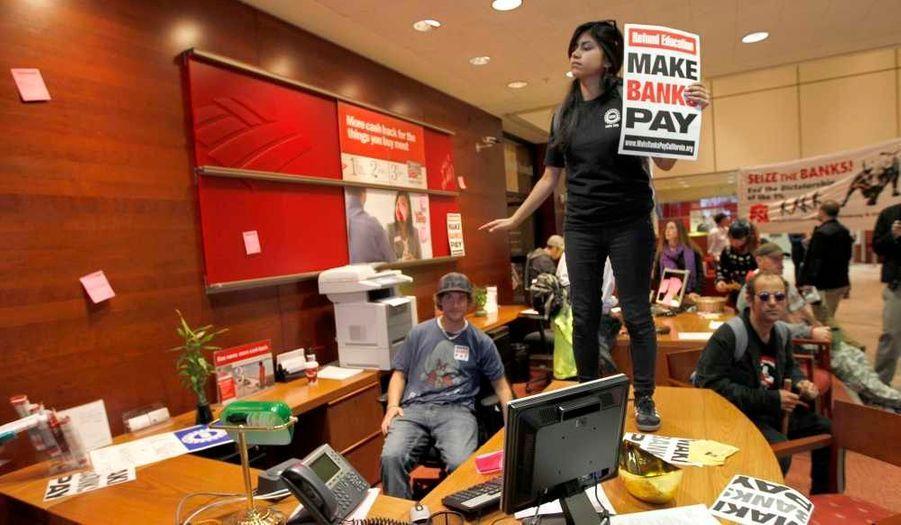 """Une """"Indignée"""" se tient sur un bureau après que le mouvement """"Occupy San Francisco"""" a envahi une filiale de la Bank of America à San Francisco, en Californie. Mercredi, 95 militants, qui avaient érigé une tente à l'intérieur de ce bâtiment situé dans le quartier financier de la ville, ont été arrêtés par la police."""
