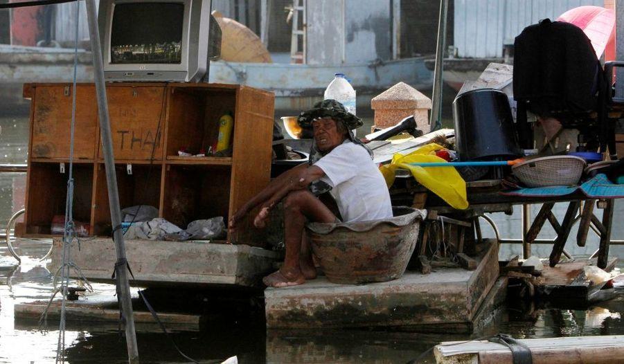 Un homme attend, assis au milieu de ses biens, dans une zone inondée de Bangkok.