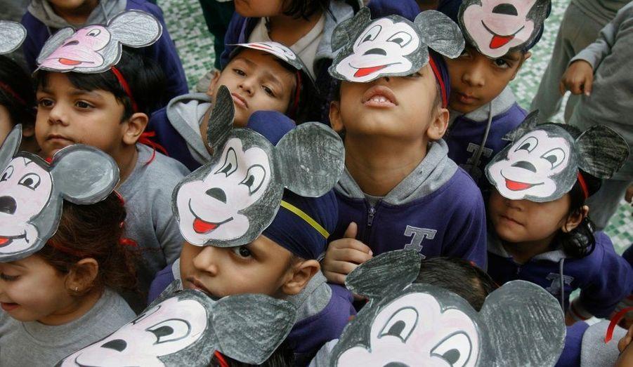 Des élèves portent des masques de Mickey à l'occasion de 83ème anniversaire du personnage imaginé par Walt Disney dans une école à Chandigarh, en Inde.