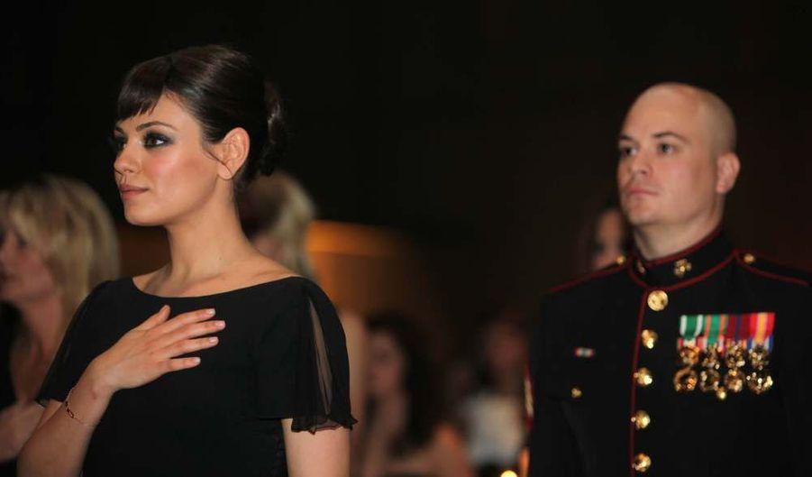 Le sergent Scott Moore et son invitée, l'actrice Mila Kunis écoutent l'hymne américain lors du bal du corps des Marines, à Greenville, en Caroline du Nord.