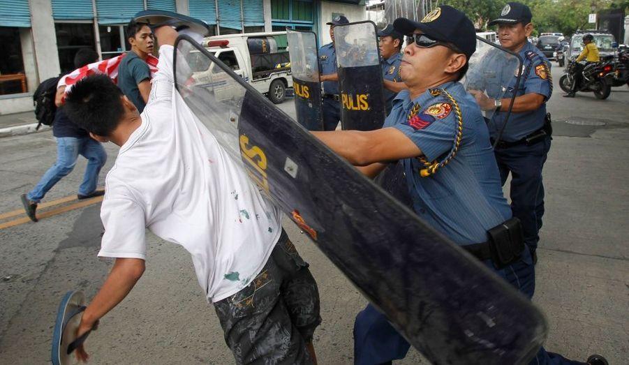 Un policier rudoie un manifestant à Manille, aux Philippines. Des dizaines d'activistes ont tenté de s'en prendre au convoi de la secrétaire d'Etat américaine, Hillary Clinton, qui est en visite dans le pays.