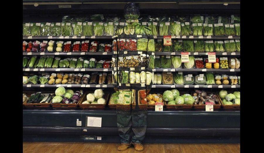 """Liu Bolin est habillé d'une combinaison se mélangeant à l'étalage de légumes d'un supermarché à Pékin. Surnommé l'""""Homme invisible"""", l'artiste est célèbre pour ses illusions d'optique, créant une forme d'art du camouflage depuis plusieurs années."""