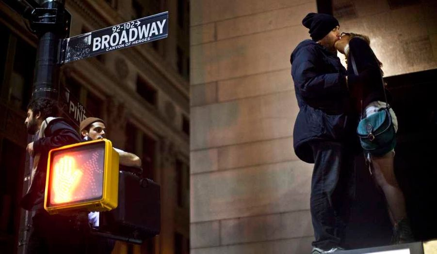 """Des manifestants pacifistes s'embrassent sur le toit d'un bus lors du raid surprise organisé par la police de New York visant à évacuer Zuccotti Park -occupé par les """"Indignés de Wall Street""""- pour cause de nettoyage."""