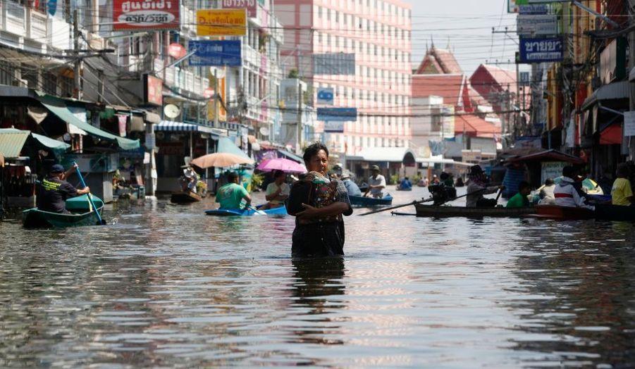 Un homme emporte ses biens dans les rues inondées de Nonthaburi, dans la banlieue de Bangkok.