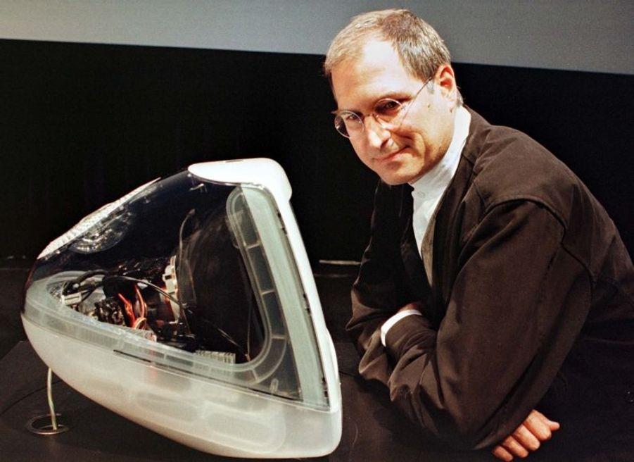 Steve Jobs pose en 2000 avec une version collector de l'iMac, descendant du Macintosh, et fer de lance de la marque dans les années 1990 et au début des années 2000.
