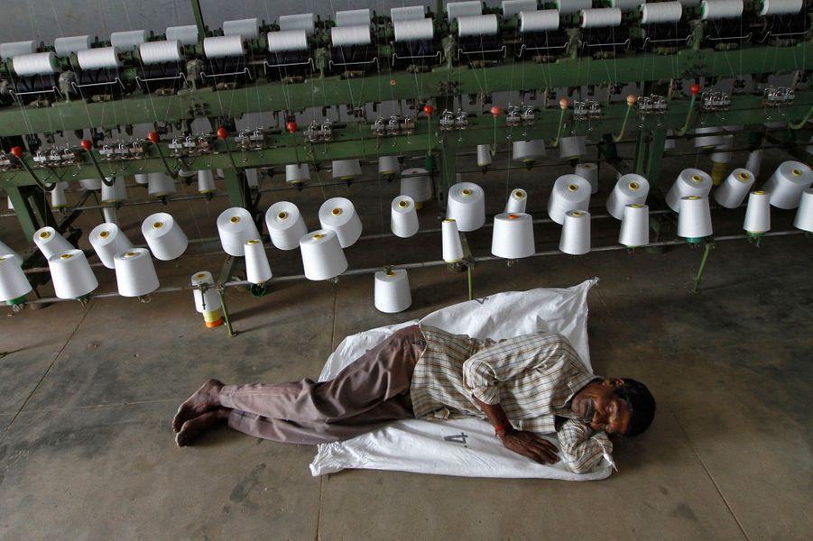 Un travailleur fait une sieste dans une usine, profitant d'une coupure de courant.