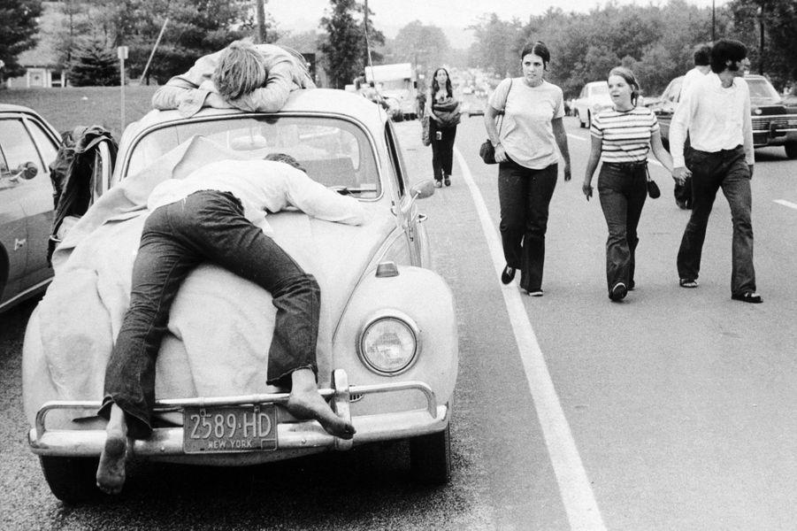 A Woodstock, en août 1969, deux festivaliers endormis sur leur Coccinelle.