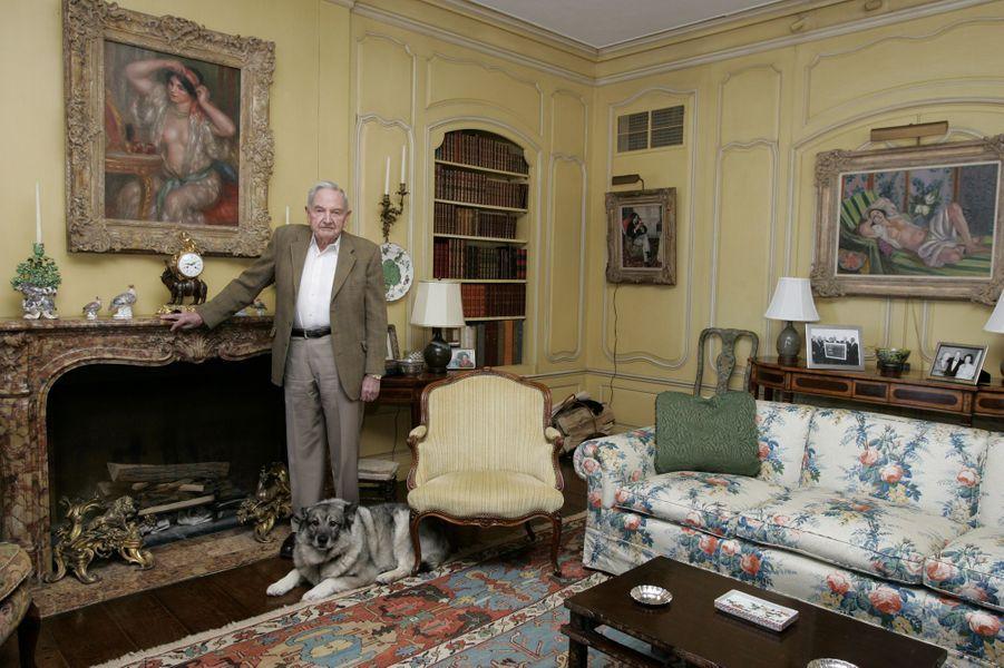"""David Rockefeller dans sa maison de Hudson Pines, située sur le domaine familial, dans la mythique propriété de Pocantica Hills : posant dans un salon avec son chien Tory, un norvegian elkhound de dix ans. Aux murs, des tableaux célèbres : à gauche, un Renoir (""""Gabrielle portant un miroir"""", 1910) ; à droite, un Pissarro (""""Portrait de Félix lisant"""", 1893) et un Matisse, """"Odalisque aux magnolias""""."""