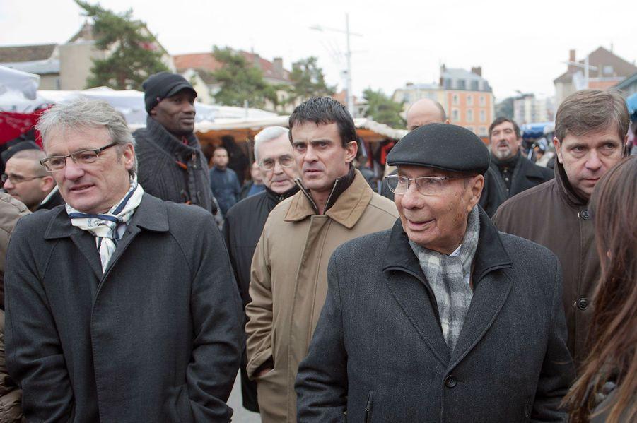 En campagne pour le candidat Jean-Pierre Bechter qui lui a succédé à la mairie de Corbeil-Essonnes, Serge Dassault croise Manuel Valls et le candidat de la gauche unie, Bruno Piriou (à g.), sur un marché en novembre 2010.