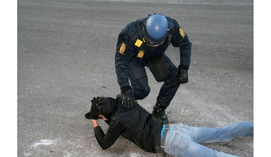 Le policier, qui l'a plaqué au sol, parvient très rapidement à le maîtriser.