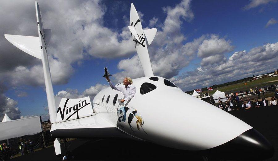La navette touristique d'où Richard Branson brandit une maquette de son lanceur de satellite.