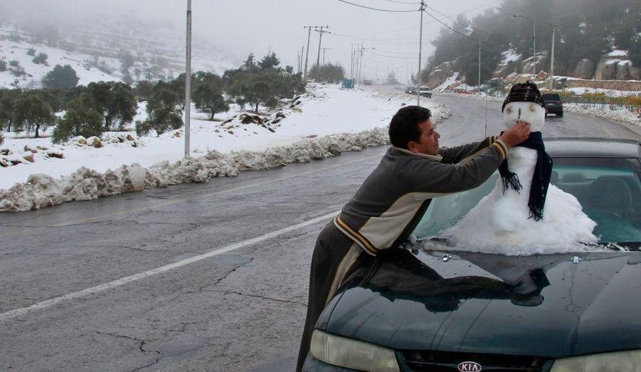 Un homme s'amuse à faire un bonhomme de neige sur sa voiture à Ajloun, en Jordanie.