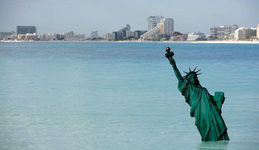 Une version en carton de la Statue de la Liberté immergée dans l'océan, près de la plage de Gaviota Azul, à Cancun. C'est ici une nouvelle performance réalisée par Greenpeace alors que se tient le sommet sur l'environnement dans la station balnéaire du Mexique.
