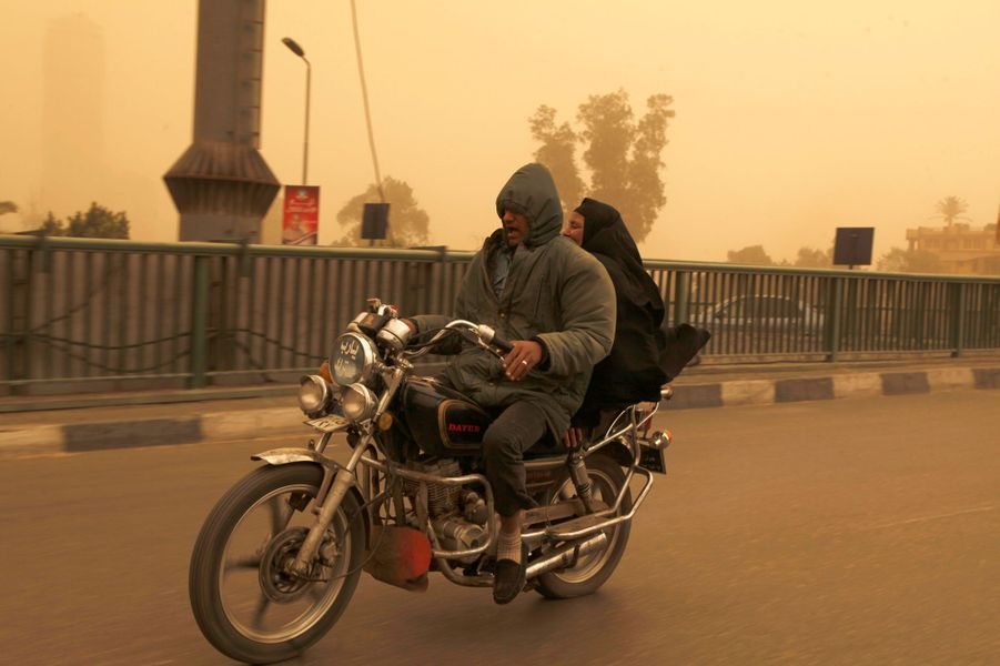 Man and a woman ride on a motorcycle over a bridge during a sand storm in Cairo