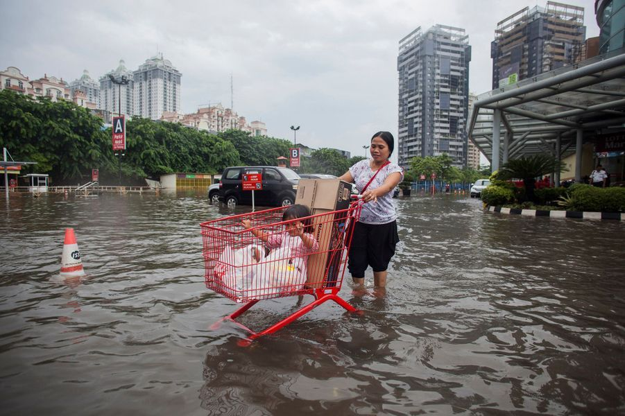Mother uses a shopping cart to transport her child and groceries through a flooded parking lot at a mall in Kelapa Gading, North Jakarta