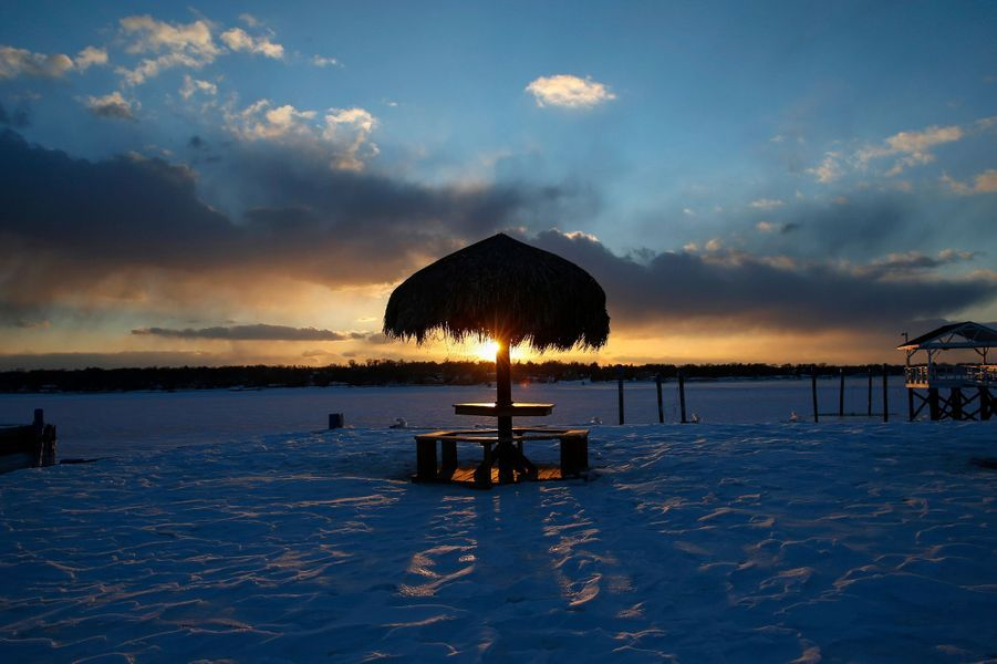 A thatched roundtable sits on a snow-covered beachfront in Port Washington, New York