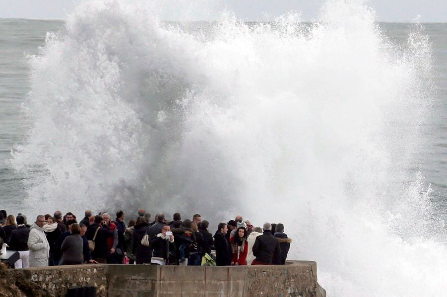 People look at waves breaking on a beach front at high tide in Biarritz