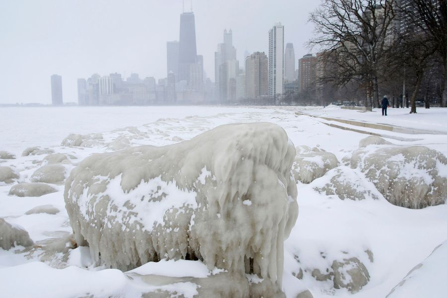 A woman walks along a path past mounds of snow and ice along Lake Michigan in Chicago
