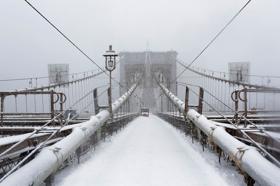 A worker clears snow on the Brooklyn bridge in New York