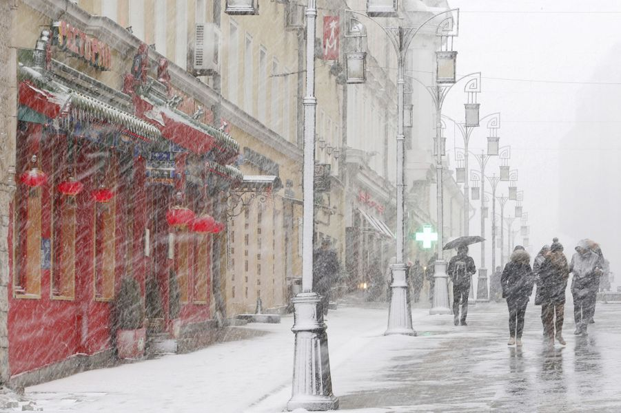 People walk during a heavy snowfall in central Moscow