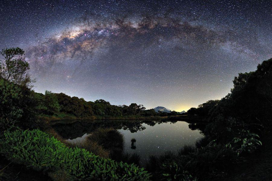 """«J'ai patienté deux ans pour parvenir à mes fins et obtenir cette image. Une Voie Lactée en arche parfaite au-dessus du sommet de la Réunion (le Piton des Neiges), un fin croissant de lune pour éclairer le premier plan et enfin une météo parfaite... Il est parfois difficile d'obtenir tous les paramètres simultanément pour réaliser le cliché de vos rêves. Cet ancien cratère -pas facile d'accès-, aujourd'hui rempli d'eau, que l'on appelle """"Piton de l'eau"""", pouvait enfin refléter les étoiles de notre galaxie.» Visitez le site de Luc Perrot :www.lucperrot.frEt sa page Facebook :www.facebook.com/lucperrotphoto"""