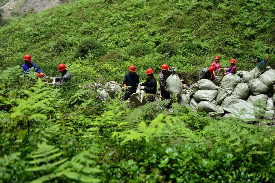 Les chinois ont pris l'habitude de jeter des déchets dans le trou. Une équipe de nettoyage s'est mise a les ramasser.
