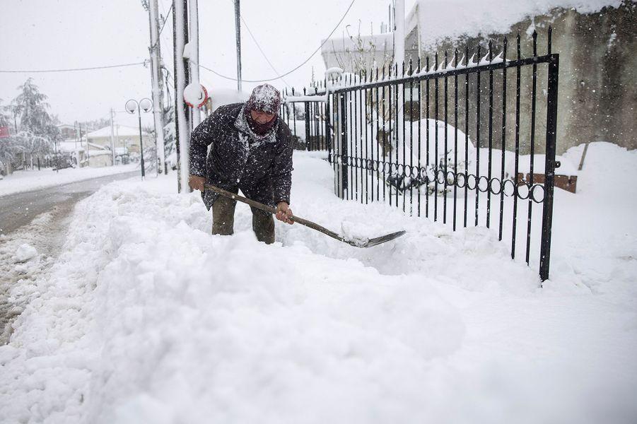 Un homme retire la neige devant chez lui dans le village deKapandriti.