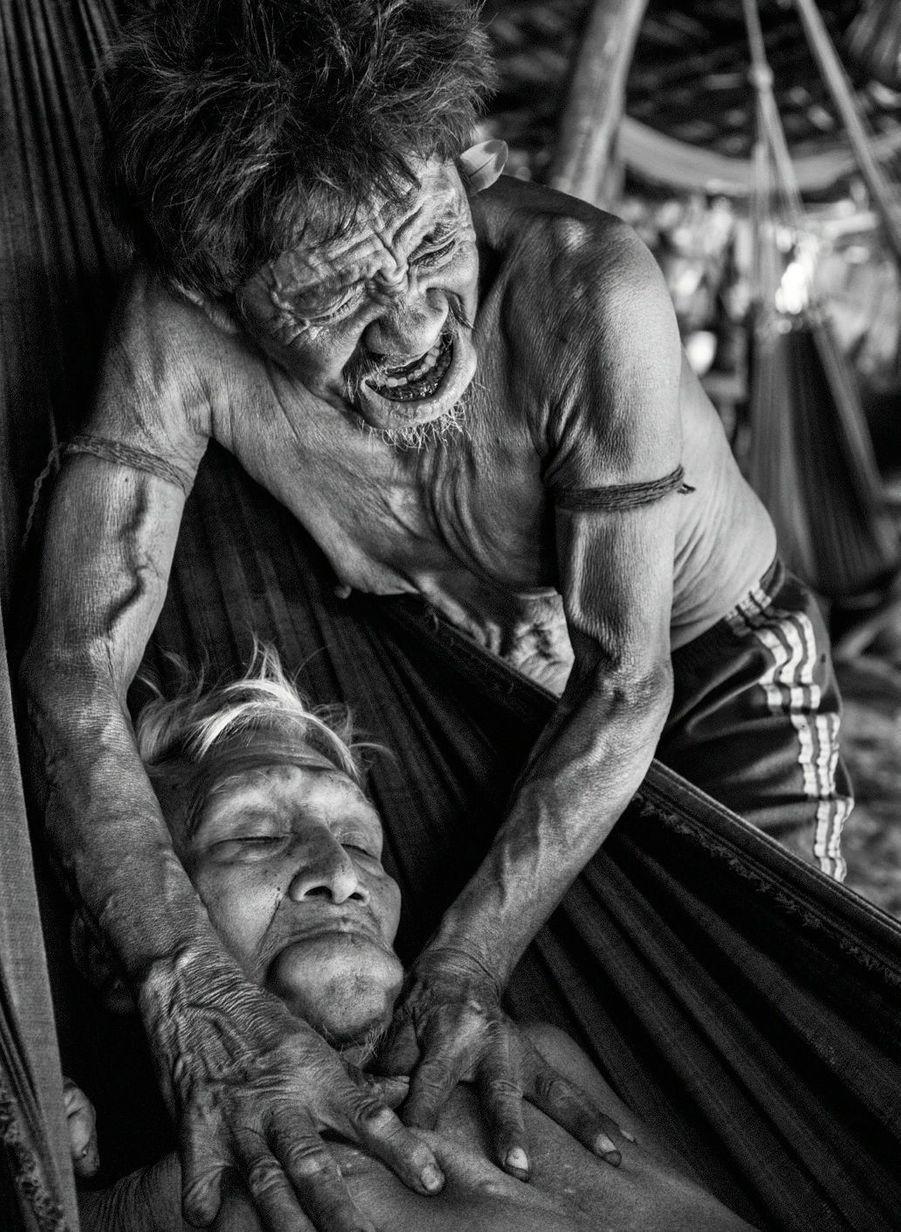 Un chaman en plein soin traditionnel, mais vêtu d'un short occidental, comme souvent aujourd'hui. Son patient et lui ont la lèvre inférieure gonflée par une chique de feuilles de tabac issues du jardin