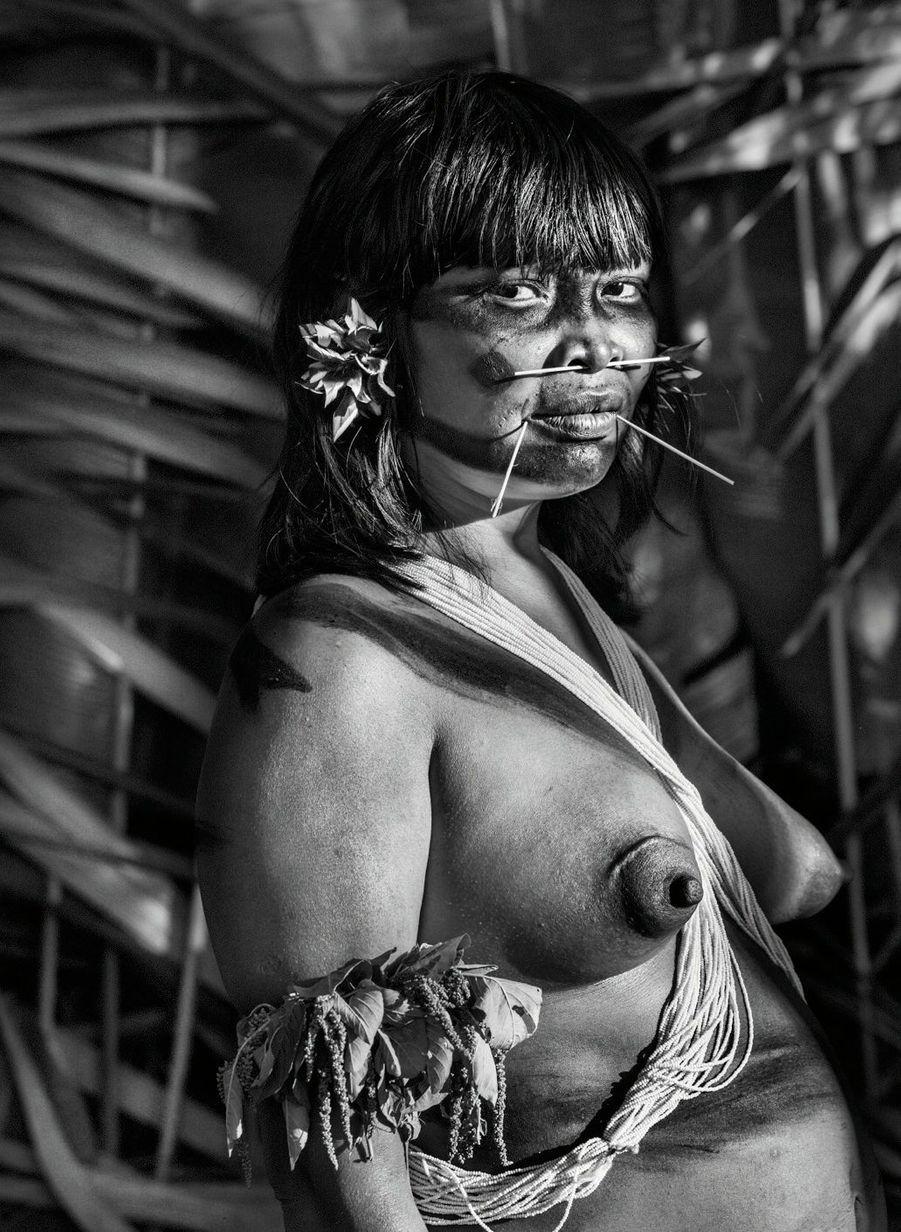 Comme toutes les femmes, elle porte une profusion de perles en bandoulière et des tiges de graminées en piercings. Fleurs et feuilles parfumées sont signe de fête.