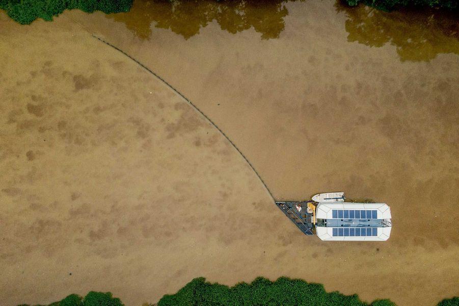 L'« Interceptor » et sa barrière courbée, en opération sur le Klang, l'un des fleuves très pollués de Malaisie.